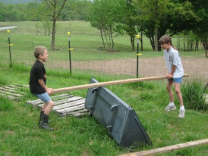Ian and Ali invented their own teeter-totter thanks to a 2x4 and the bucket to Darin's tractor.